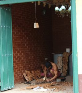 An image of a man carving wood in his shop to sell to tourists visiting Trinidad, Cuba.