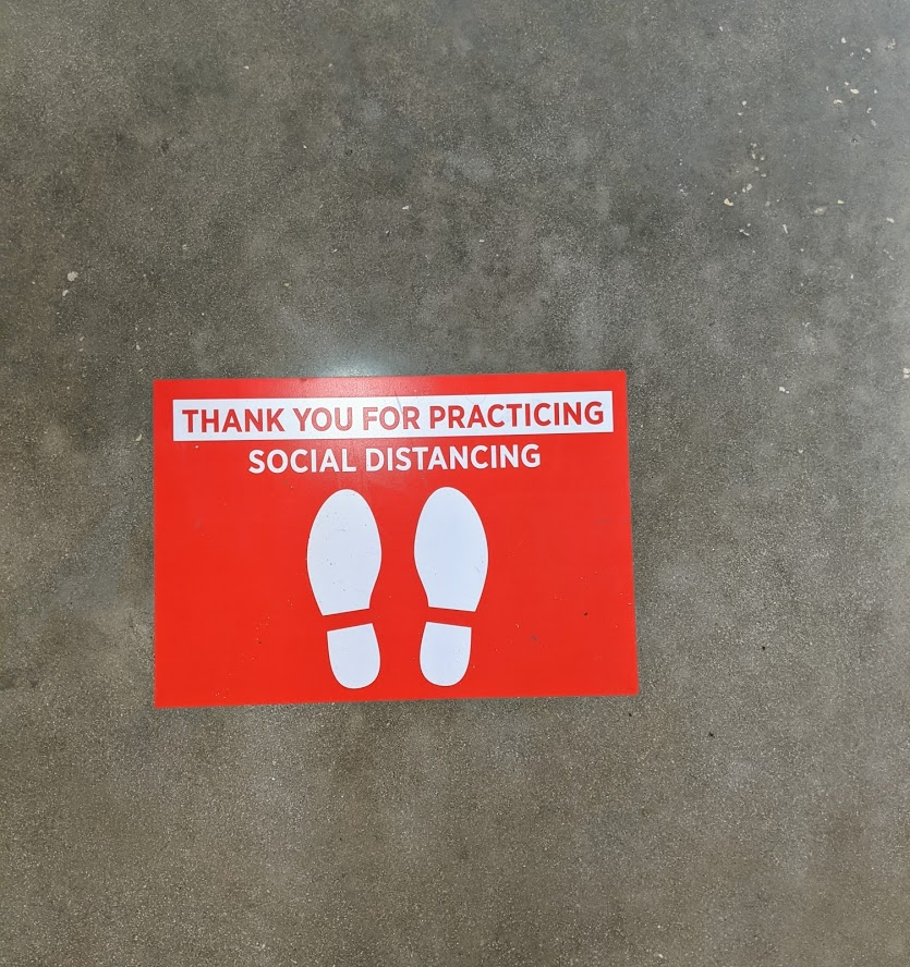 Sticker on the grocery store floor reminding shoppers to maintain physical distancing, photo credit Iris Gonzalez