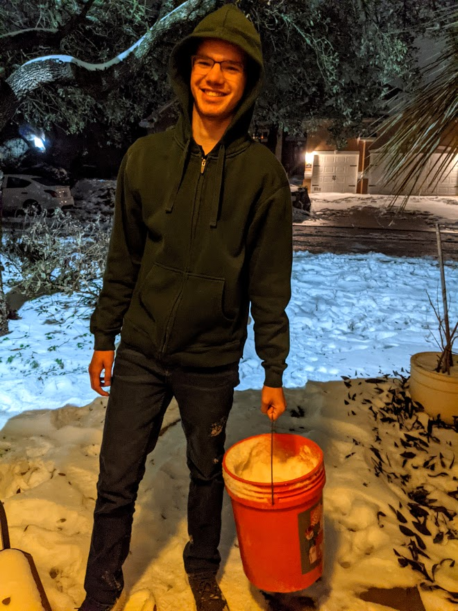 Our son bringing in buckets of snow to melt for water, photo credit Iris Gonzalez
