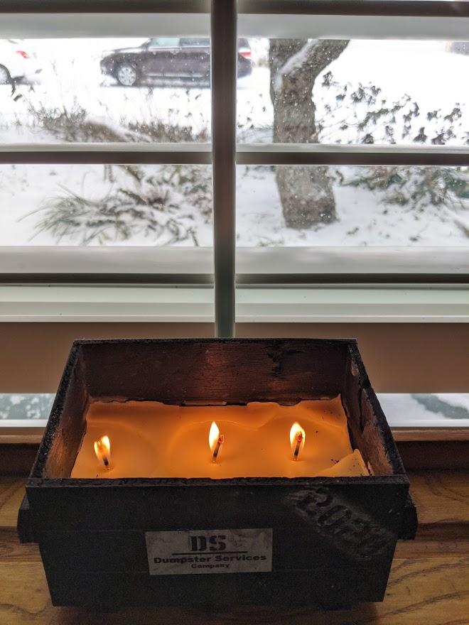 The 2020 dumpster fire candle burns as it snows again, photo credit Iris Gonzalez